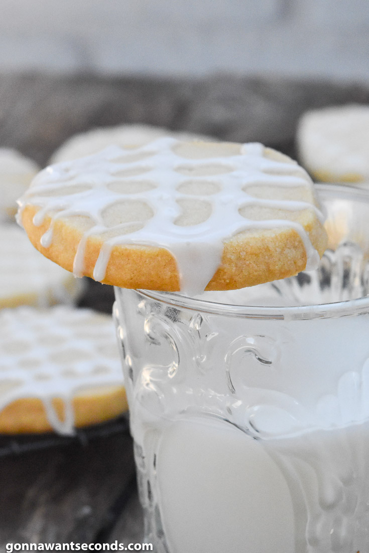 almond shortbread cookies placed on top of a glass of milk