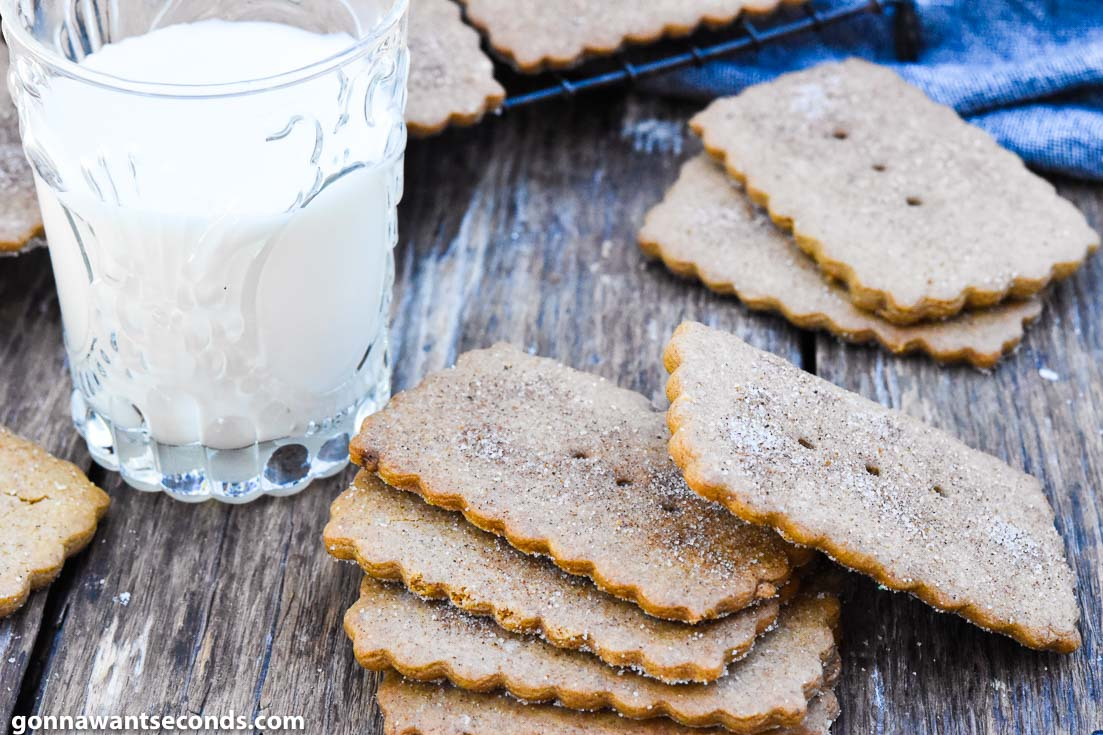 biscoff cookies piled on top of each other with a glass of milk on the side