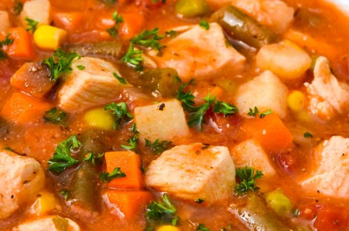 Chicken vegetable soup in a white bowl
