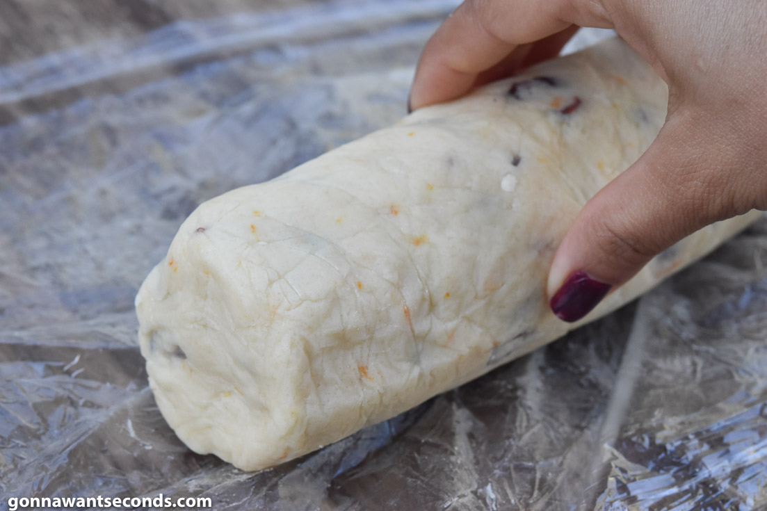 How to make Cranberry orange shortbread cookies, rolling the dough to make a log