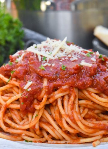 Italian spaghetti topped with cheese, on a plate