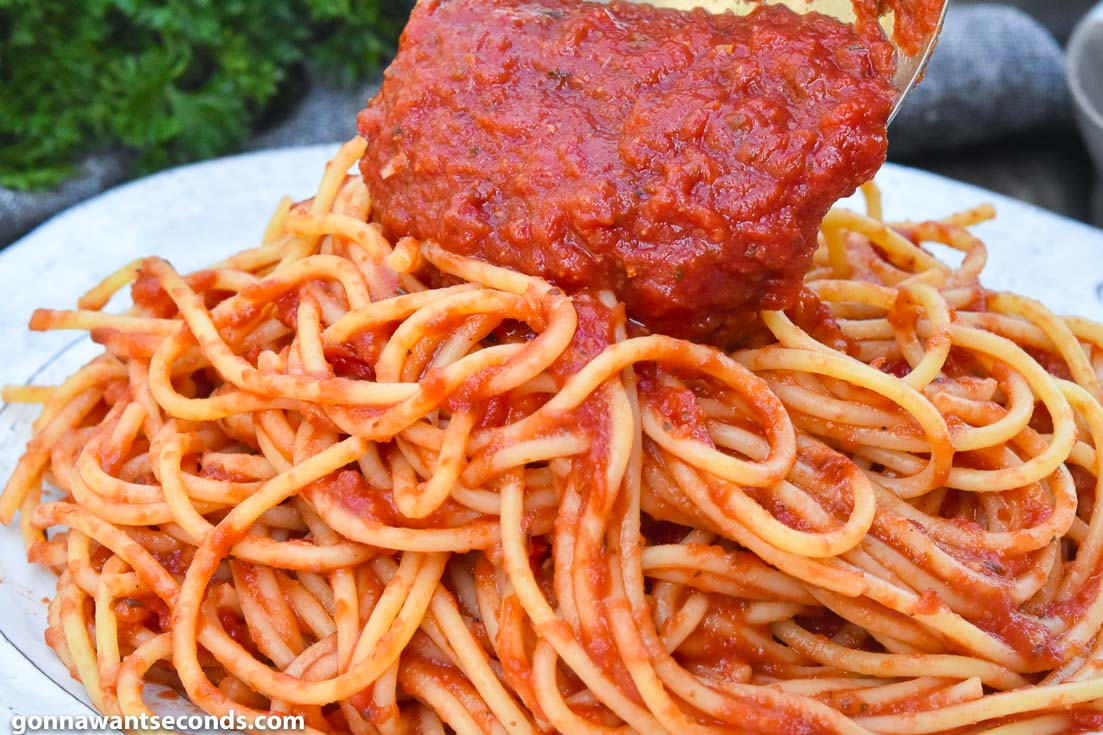 Adding sauce to Italian spaghetti on a plate