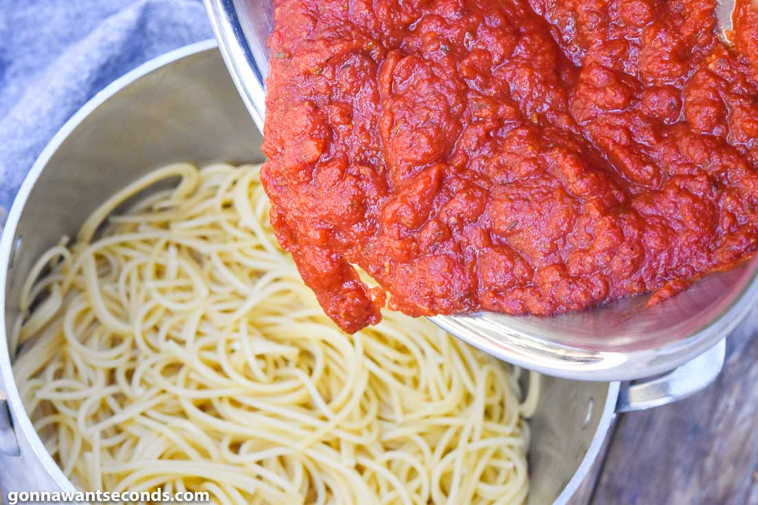 Adding sauce to Italian spaghetti in a pot
