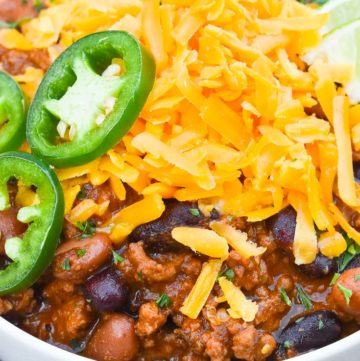 Pioneer Woman Chili topped with cheese, jalapeno, and lime, on a bowl