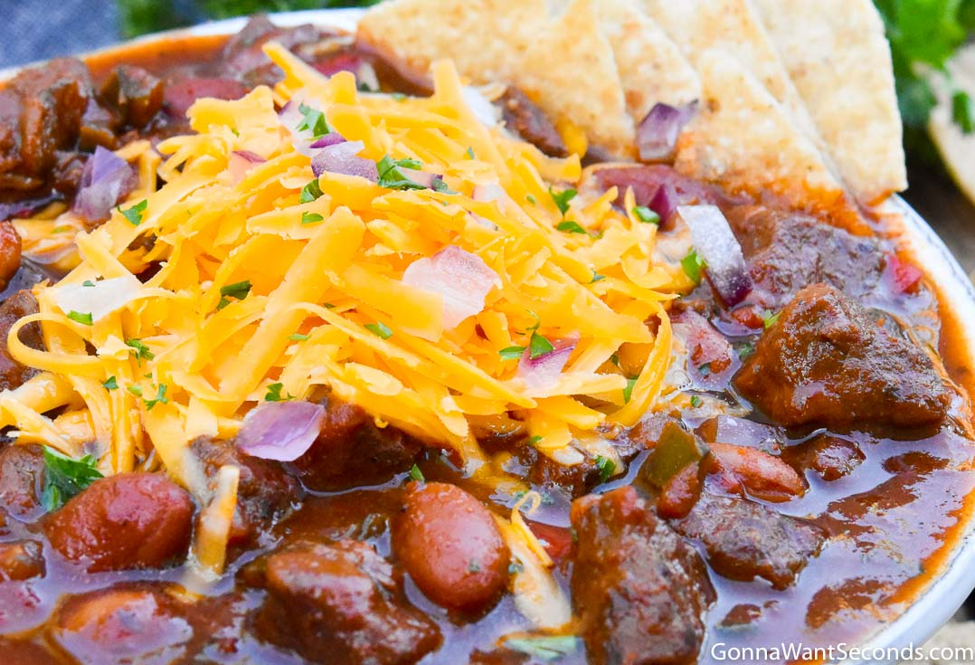 Steak Chili with toppings, on a white bowl