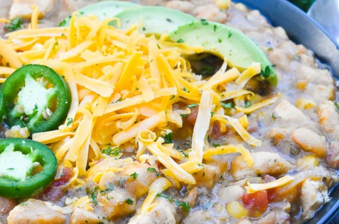 White Chicken Chili topped with avocados, shredded cheese, and jalapenos, in a bowl
