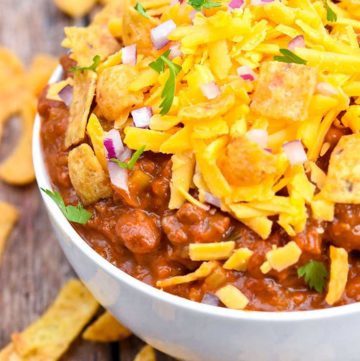 Boilermaker chili topped with shredded cheese, Fritos, and onions, in a bowl