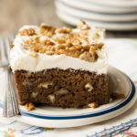 A single serving of Applesauce Cake with frosting and chopped pecans on top, on a saucer