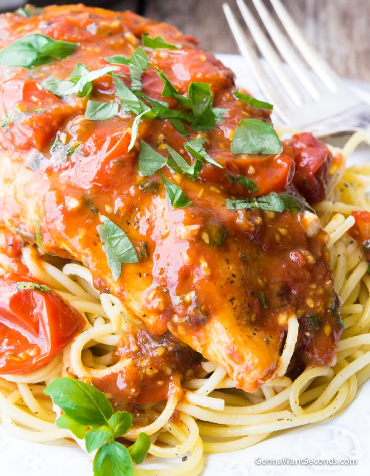 Balsamic Chicken with sauce, garnished with freshly chopped basil, topped on a plate of pasta