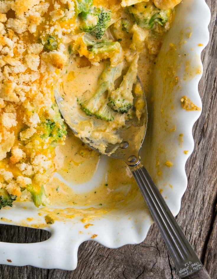 Broccoli Cauliflower Casserole in a baking dish with a serving spoon scooped a portion