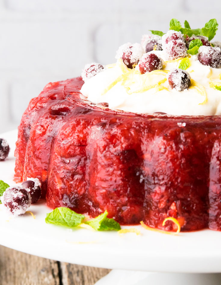 Cranberry Jello Salad with Lemon Cream Topping, garnished with sugared cranberries and mint leaves, on a cake stand
