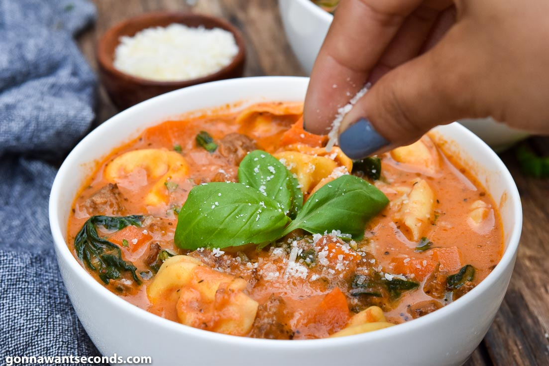 Creamy tortellini soup topped with fresh basil, in a bowl