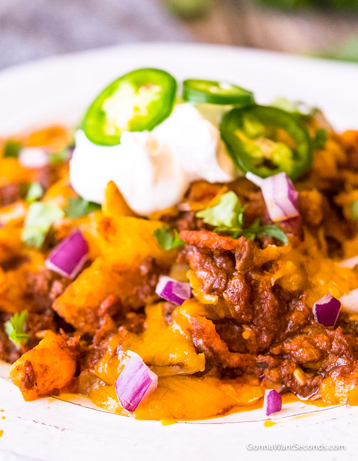 Frito Pie topped with a dollop of sour cream and sliced jalapenos on a saucer