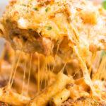 Spoon scooping Olive Garden Five Cheese Ziti Al Forno in a casserole