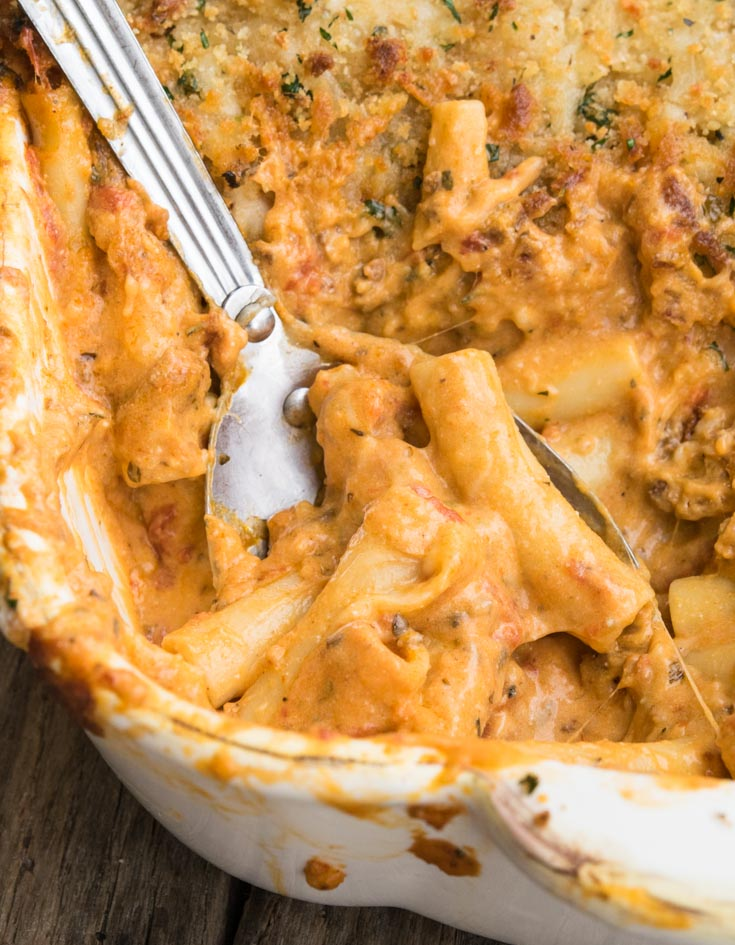 Spoon scooping Olive Garden Five Cheese Ziti Al Forno in a casserole