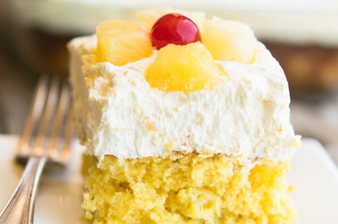 A slice of Pineapple Sunshine Cake with whipped topping, topped with pineapple and cherry on a plate