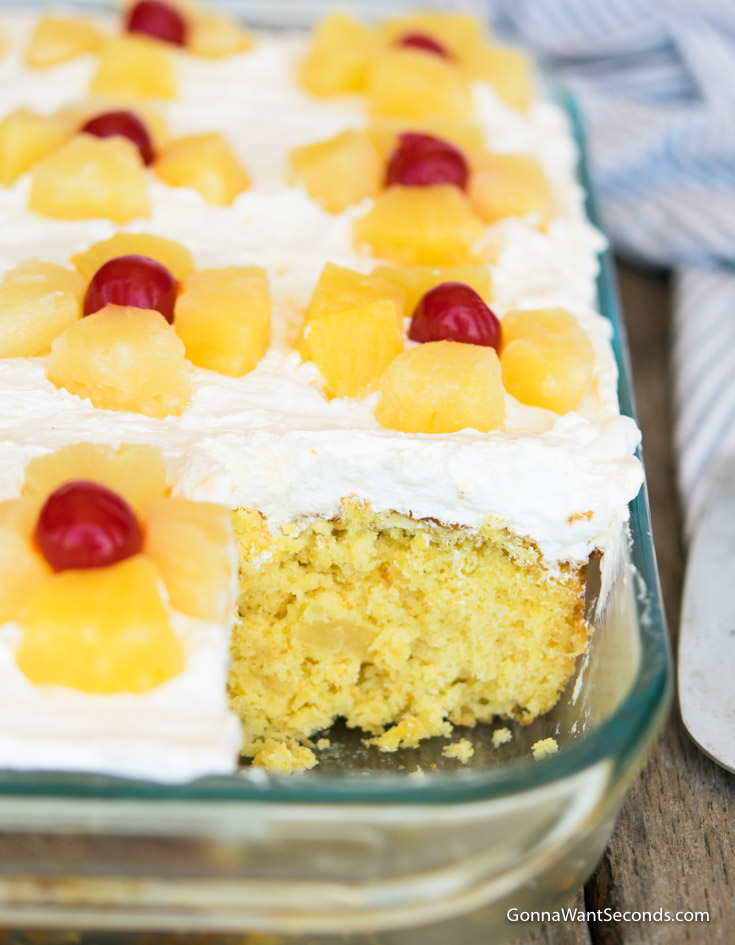 Pineapple Sunshine Cake with whipped topping, topped with pineapples and cherries in 9x13 sheet pan