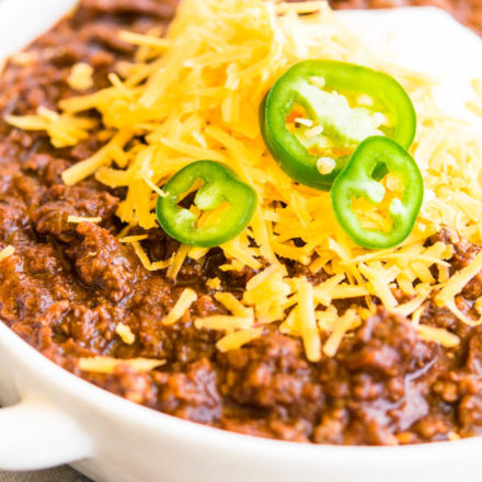 Bowl of Texas Chili topped with shredded cheese, sliced jalapenos, and dollop of sour cream