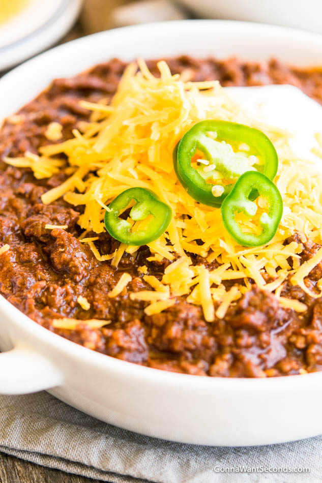 Bowl of Texas Chili topped with shredded cheese, sliced jalapenos, and dollop of sour