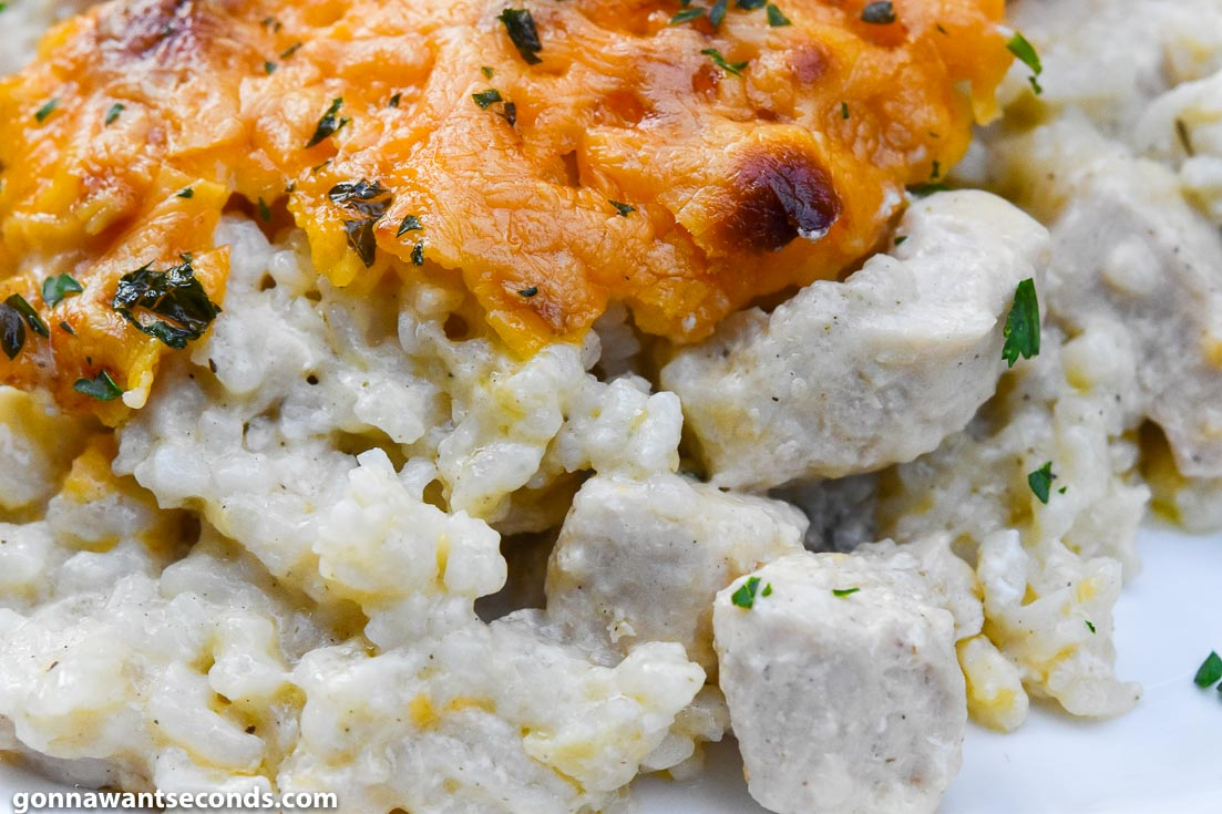 Chicken and rice casserole topped with melted cheese, on a plate