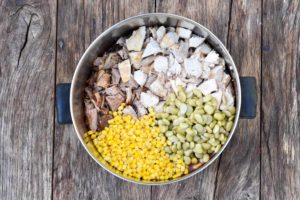 How to make Brunswick stew, adding corn and the rest of ingredients to the pot