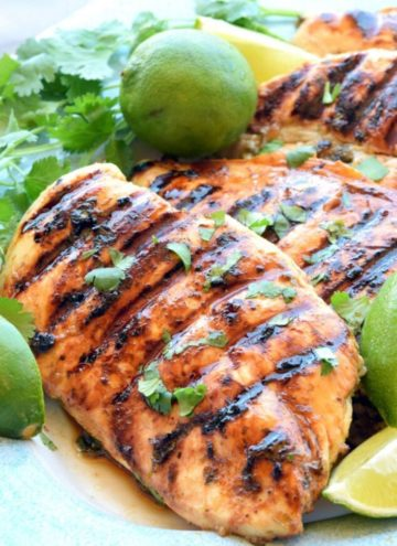 Cilantro lime chicken garnished with lime wedges and cilantro on a plate