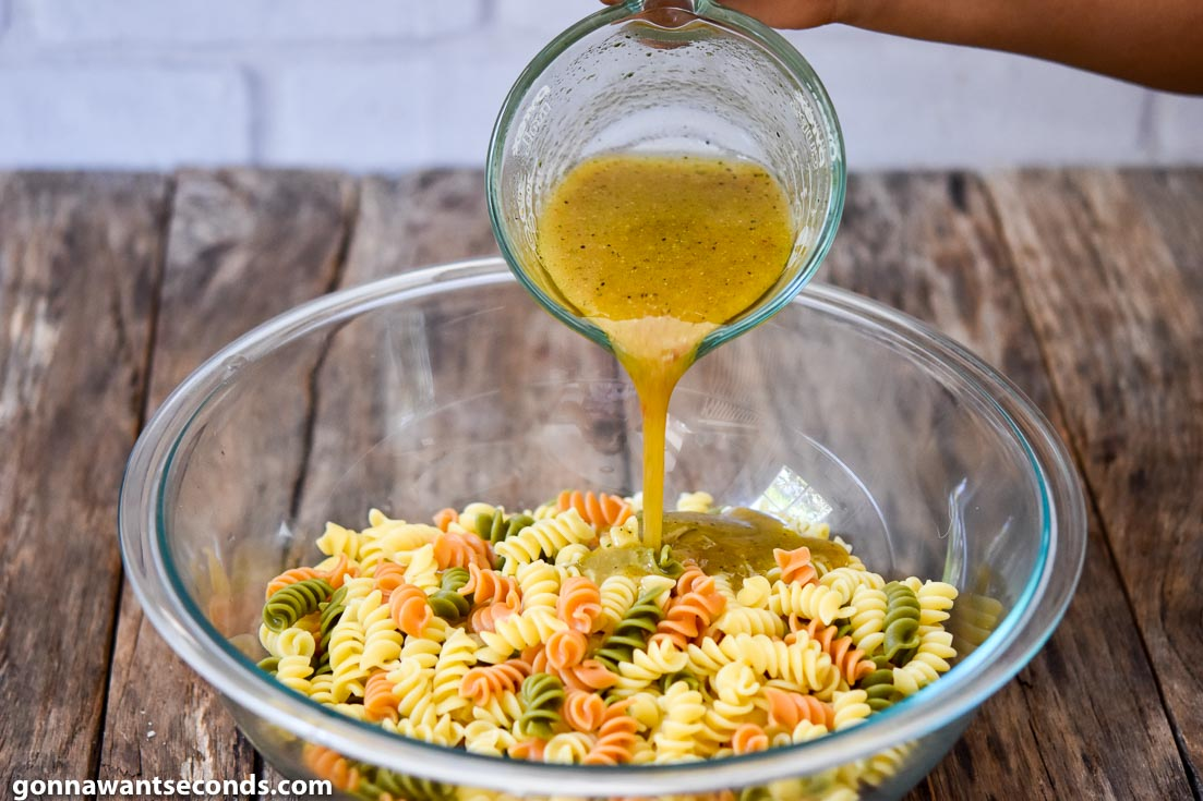 How to make Pasta Salad with Italian Dressing, pouring Italian dressing to the pasta