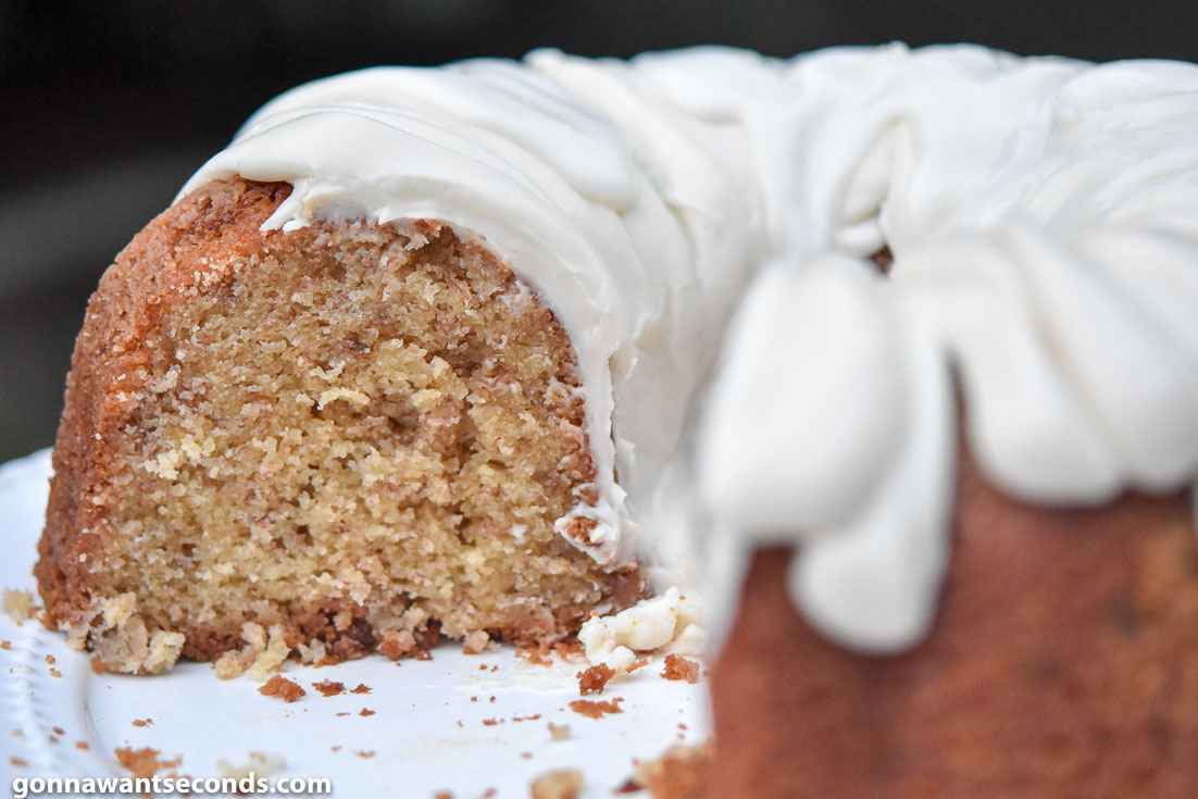 Whole Banana Pound Cake cut in half, on a cake stand