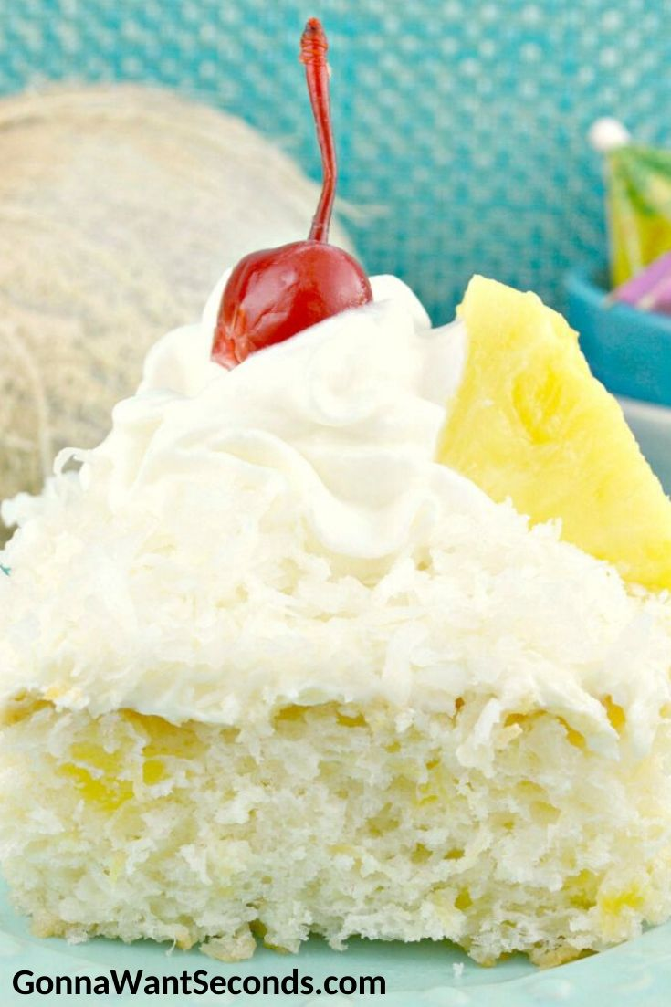A slice of Pina Colada Cake with frosting, topped with a cherry, a pineapple, and a cocktail umbrella
