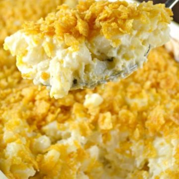 ladle scooping scalloped potatoes from the casserole