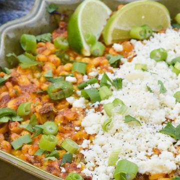 Mexican street corn casserole topped with cheese and lime