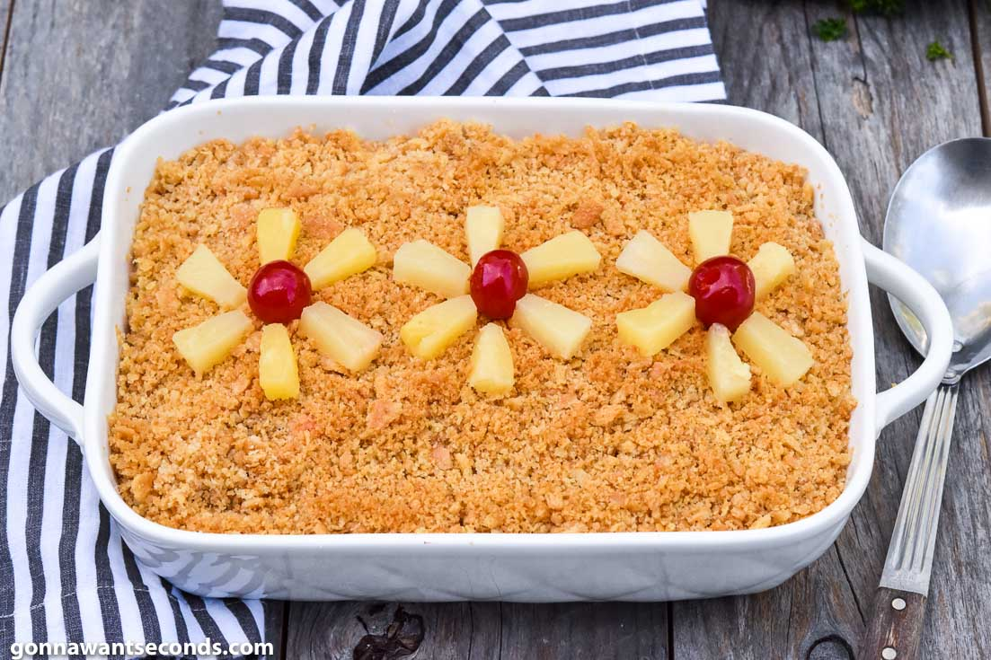 Pineapple Casserole topped with pineapple tidbits and cherries