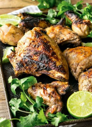 Pollo Asado with fresh cilantro and lime on a baking sheet