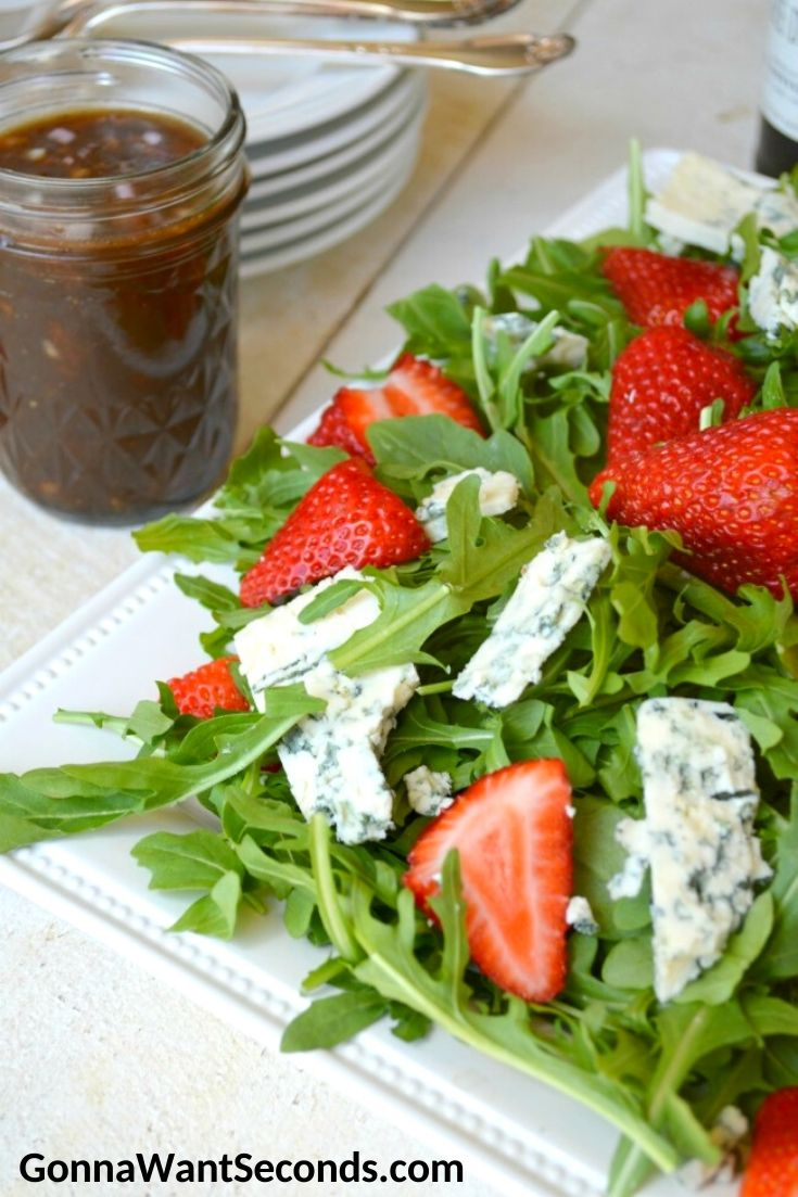 Strawberry Salad with a jar of homemade vinaigrette on the side