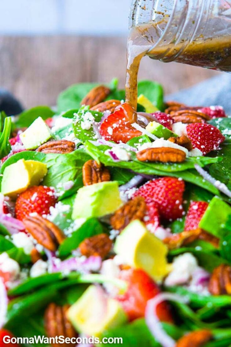 Pouring balsamic vinaigrette over strawberry spinach salad