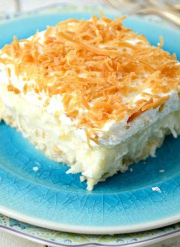 A slice of Coconut Cream Pie Bars on a blue plate
