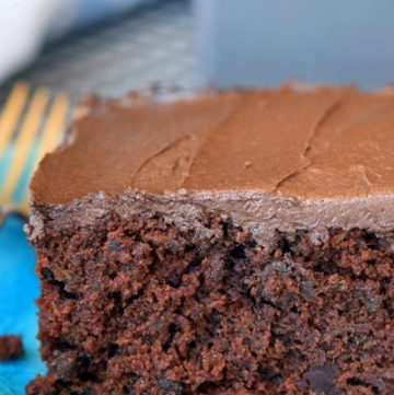 A slice of chocolate zucchini cake on a blue plate