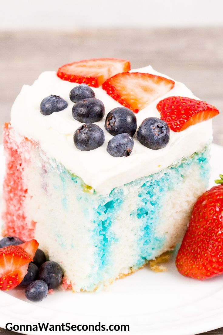 A slice of Red White and Blue Poke Cake topped with strawberries and blueberries, on a plate