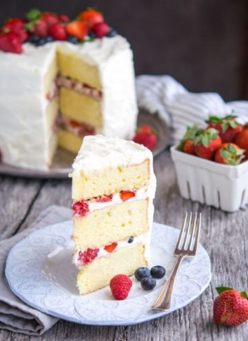 A slice of Berry Chantilly Cake with the whole cake at the back