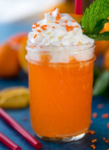orange creamsicle drink topped with whipped cream and sprinkles