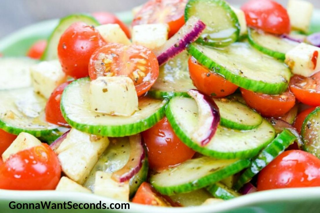 cucumber tomato salad in a shallow green bowl