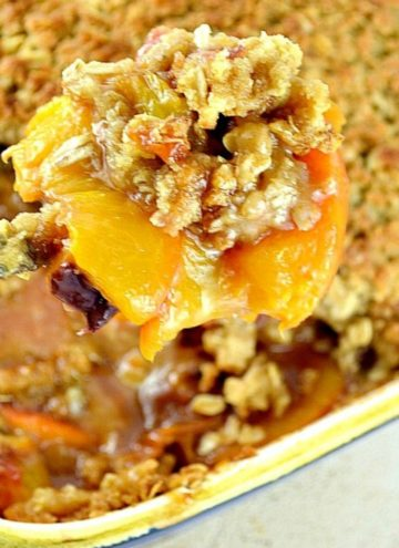 Scooping peach crisp from a casserole