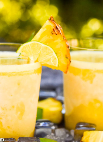 Two glasses of Pineapple Margaritas topped with a slice of pineapple and lime