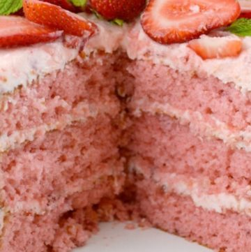 Whole strawberry layer cake sliced exposing layers
