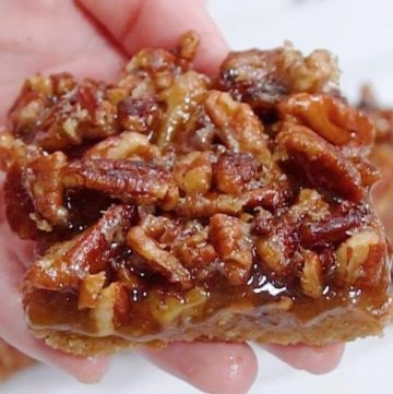 Hand holding a slice of Pecan Pie Bars