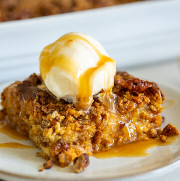 A slice of pumpkin dump cake with pecans, topped with vanilla ice cream and drizzled with caramel