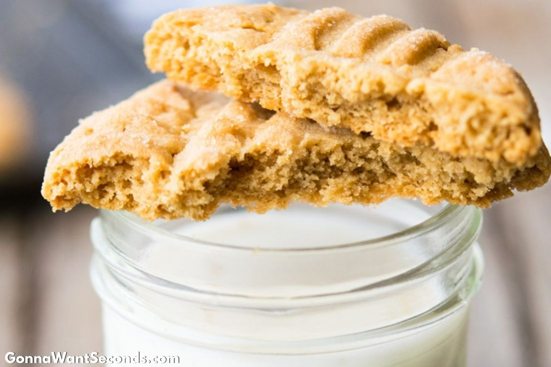 One Classic Peanut Butter Cookies broken in half placed top of a glass of milk