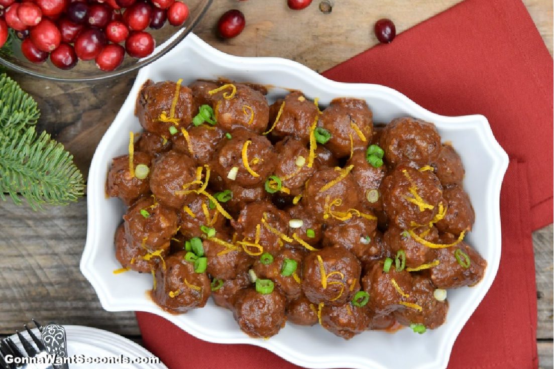 Cranberry Meatballs in a serving dish, with fresh cranberries on the side