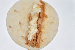 How to make Sour cream chicken enchiladas, rolling the fillings in the tortillas