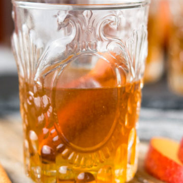 A glass of Apple Pie Moonshine with cinnamon stick